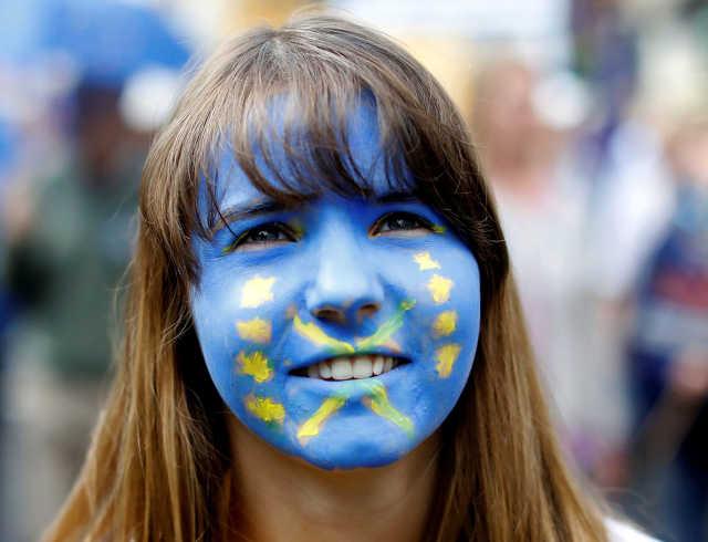 Az Európai Unió zászlója egy tüntető arcán