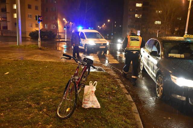 Taxi elejének tekert záróvonalon keresztül egy kerékpáros