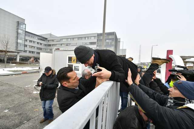 Gréczy Zsolt, a DK-s országgyűlési képviselő átmászik a kerítésen az MTVA Kunigunda utcai székházának területére.
